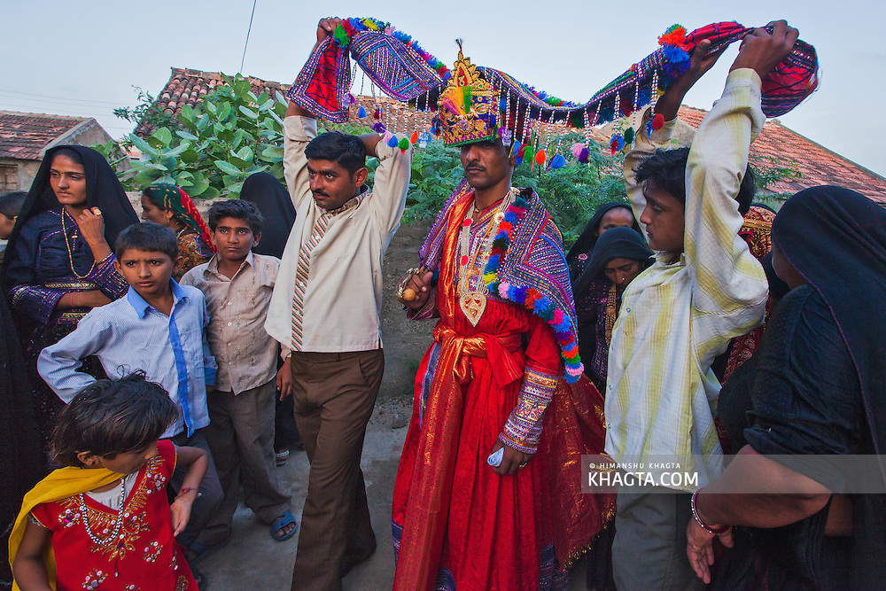 The groom enters his home after getting married with a traditional colourful costume.