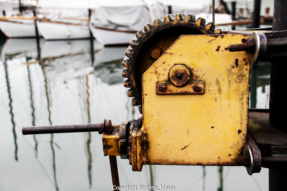 Rusting old yellow tackle at the harbor, with sailboat and their masts mirroring in the water, on a cold wintersday in Denmark