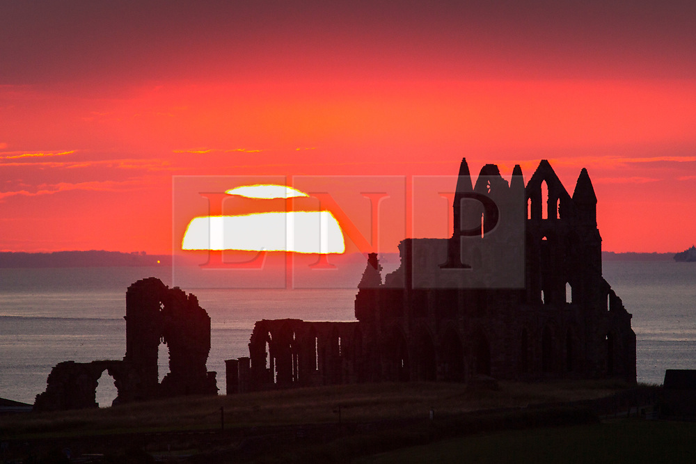 © Licensed to London News Pictures. 17/07/2018. Whitby UK. The sun sets behind the Gothic ruins of Whitby Abbey on the Yorkshire coast as the UK prepares for another hot day. Photo credit: Andrew McCaren/LNP
