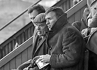 Paddy Crerand, assistant team manager, Manchester United, nearest camera, with the legendary scout, Bob Bishop, who discovered George Best, cloth cap and cigarette, at a match at the Oval, the ground of Glentoran FC, 24th November 1973. They were there to cast their eye on any promising players. 197311240722.<br />