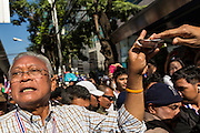"15 JANUARY 2014 - BANGKOK, THAILAND: SUTHEP THAUGSUBAN, former Deputy Prime Minister of Thailand and leader of the Shutdown Bangkok anti-government protests, accepts cash from supporters on Sukhumvit Road in Bangkok during a protest march. Tens of thousands of Thai anti-government protestors continued to block the streets of Bangkok Wednesday to shut down the Thai capitol. The protest, ""Shutdown Bangkok,"" is expected to last at least a week. Shutdown Bangkok is organized by People's Democratic Reform Committee (PRDC). It's a continuation of protests that started in early November. There have been shootings almost every night at different protests sites around Bangkok. The malls in Bangkok are still open but many other businesses are closed and mass transit is swamped with both protestors and people who had to use mass transit because the roads were blocked.    PHOTO BY JACK KURTZ"