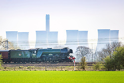 © Licensed to London News Pictures. 19/04/2018. Selby UK. The 1923 coal powered Flying Scotsman passes the recently decommissioned 1970's coal powered Eggborough power station near Selby this afternoon. The famous locomotive is travelling from London Kings Cross to Scarborough on it's first day of a tour of Britain. Photo credit: Andrew McCaren/LNP