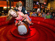 Kelsey Milan, left, and Angela Partin, right, both of Ft. Worth, ride a mechanical bull at The Trophy Room on Sixth Street in Austin, TX on Saturday, March 15, 2014 during the 2014 SXSW music festival.<br /> (Ashley Landis/Special contributor)