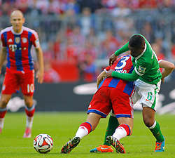 MUNICH, GERMANY - OCTOBER 18: Xabi Alonso of Bayern Munich and Cedric Makiadi of Werder Bremen compete for the ball  during the Bundesliga match between Bayern Munich and Werder Bremen. October 18, 2014 in Munich, Germany. Photo mandatory by-line: Mitchell Gunn