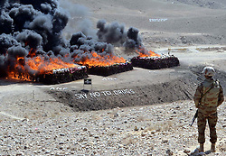 October 20, 2016 - Pakistan - QUETTA, PAKISTAN, OCT 20: Anti-Narcotics Force (ANF) and Frontier Corps (FC) officials .stand alert near burning pile of confiscated drugs during the incineration ceremony of seized .illegal drugs, held at Kuch Mor located on Quetta Cantonment area on Thursday, October 20, .2016. The law enforcement agency burnt a large quantity of narcotics and alcohol seized in .different parts of the province. (Credit Image: © PPI via ZUMA Wire)