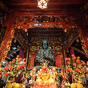 A large bronze statue and offerings at Quan Thanh Temple in Hanoi. The statue, measuring nearly 4 meters tall and weighing nearly 4 tons was cast in 1677 and depicts Huyen Thien Tran Vo, the God who administered the North and after whom the temple was originally named. The Taoist temple dates back to the 11th century and is located close to West Lake (Ho Tay).