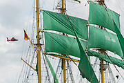 A U.S. Coast Guard helicopter flies past the massive sails of the German Barque Alexander von Humboldt II during the parade of sails kicking off the Tall Ships Charleston festival May 18, 2017 in Charleston, South Carolina. The festival of tall sailing ships from around the world will spend three-days visiting historic Charleston.