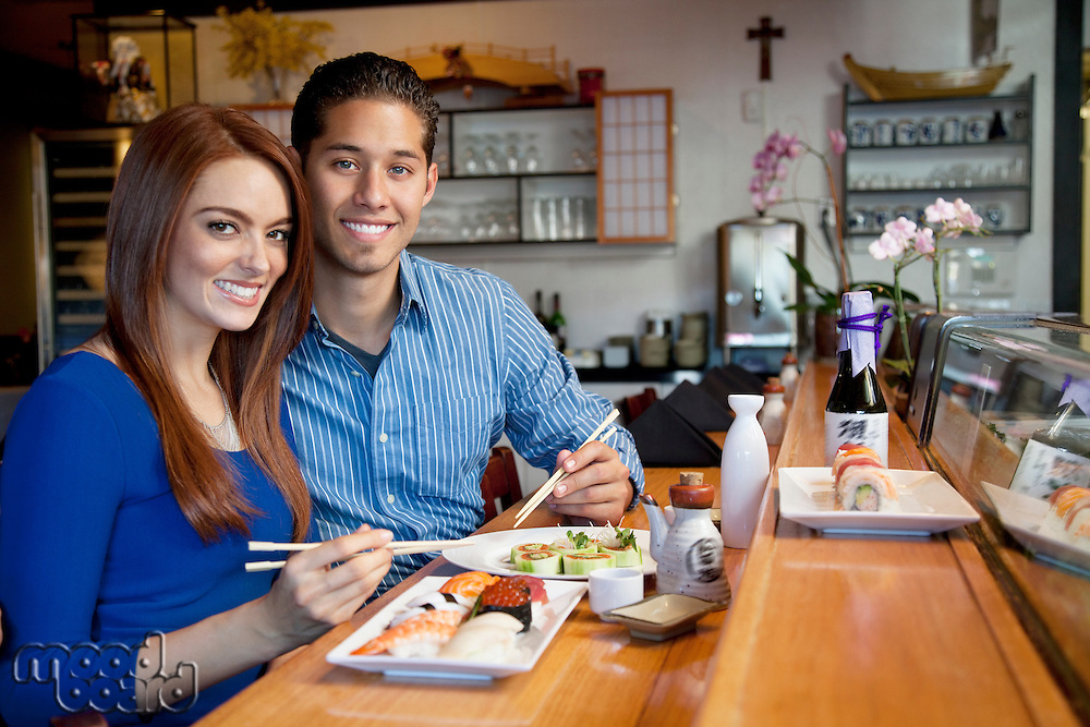 Portrait of young couple eating Japanese cuisine in restaurant