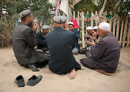 Uyghur Sufi men praying at Imam Asim Tomb in the Taklamakan desert. Xinjiang Uyghur autonomous region, China.