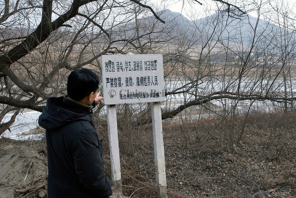 A North Korean defector near Tumen in China, reading a warning sign next to the frozen Tumen river which marks the border with North Korea. He escaped his country a first time in 1986, was caught by the Chinese police and sent back to North Korea where he was condemned to five years in the infamous Yodok labour camp. He escaped again to China in 1997, and finally arrived in South Korea in 2001. He often comes back to China to help fellow defectors to reach South Korea. The sign, written in Korean and Chinese, reads: It is forbidden to give shelter, to help or to hire people who cross the river.