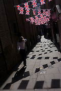 Lone woman walks beneath British Union Jack flags strung together across a London alleyway, near Bond Street.