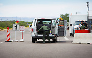 An agent searches a shuttle van at the I-19 U.S. Border Patrol checkpoint near Tubac, Ariz., July 16. The checkpoint is located about 25 miles north of the U.S.-Mexico border. NANCY WIECHEC