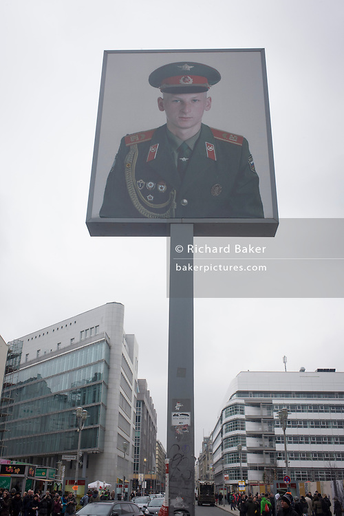 "The portrait of a Soviet soldier sits high above modern Friedrishstrasse in modern Berlin at the location of  the former Checkpoint Charlie, the former border between Communist East and West Berlin during the Cold War. The Berlin Wall was a barrier constructed by the German Democratic Republic (GDR, East Germany) starting on 13 August 1961, that completely cut off (by land) West Berlin from surrounding East Germany and from East Berlin. The Eastern Bloc claimed that the wall was erected to protect its population from fascist elements conspiring to prevent the ""will of the people"" in building a socialist state in East Germany. In practice, the Wall served to prevent the massive emigration and defection that marked Germany and the communist Eastern Bloc during the post-World War II period."