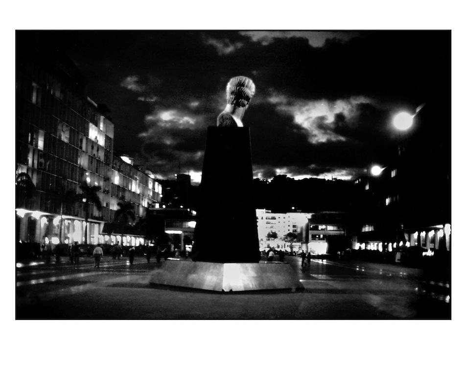 """Autor de la Obra: Aaron Sosa<br /> Título: """"Serie: Venezuela Cotidiana""""<br /> Lugar: Plaza Caracas, Caracas - Venezuela <br /> Año de Creación: 2003<br /> Técnica: Captura digital en RAW impresa en papel 100% algodón Ilford Galeríe Prestige Silk 310gsm<br /> Medidas de la fotografía: 33,3 x 22,3 cms<br /> Medidas del soporte: 45 x 35 cms<br /> Observaciones: Cada obra esta debidamente firmada e identificada con """"grafito – material libre de acidez"""" en la parte posterior. Tanto en la fotografía como en el soporte. La fotografía se fijó al cartón con esquineros libres de ácido para así evitar usar algún pegamento contaminante.<br /> <br /> Precio: Consultar<br /> Envios a nivel nacional  e internacional."""