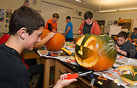 Ryan Steele puts finishing touches on his pumpkin during carving with Jane Connelly's 7th grade Maple Team at Laconia Middle School.  Approximately 400 pumpkins will be carved by students to add to the Tower at Pumpkin Fest on Saturday.  (Karen Bobotas/for the Laconia Daily Sun)