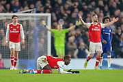 Chelsea midfielder Jorginho (5) (not in picture) shoves Arsenal forward Nicolas Pépé (19) to the ground, Arsenal players protest to the referee for a foul, during the Premier League match between Chelsea and Arsenal at Stamford Bridge, London, England on 21 January 2020.
