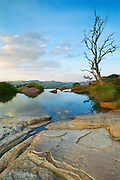 "Near the Cradle of Humankind World Heritage Site (where the 2.3-million year-old fossil Australopithecus africanus - nicknamed ""Mrs. Ples"" - was found in 1947), a Highveld summer sunset is reflected in the pond of a pure spring near Tonquani Kloof in the ancient quartzites of the Magaliesberg mountain range northwest of Johannesburg.  This area has been occupied by humans for more than 2 million years.  The range itself has a much longer geological history that began as sedimentary deposits that were later consolidated and tilted under the forces of a massive upwelling of molten magma.  This view is to the north.  South Africa. Nikon F4, 28-70/3.5-4.5D. Kodak EPP."
