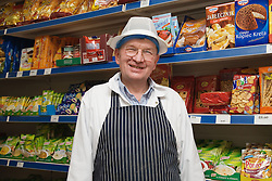 Polish shop owner standing in front of well stocked shelves of Polish food,