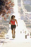 Woman running up a hill on a city street.  Seattle, WA.