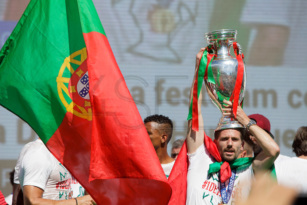 Portuguese player Adrien balancing  the Euro Cup in his head while celebrating with supporters at Alameda Dom Afonso Henriques, in Lisbon. Portugal's national squad won the Euro Cup the day before, beating in the final France, the organizing country of the European Football Championship, in a match that ended 1-0 after extra-time.