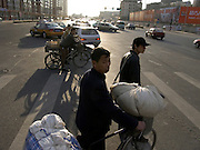 man with a loaded bicycle waiting to cross the road China Beijing
