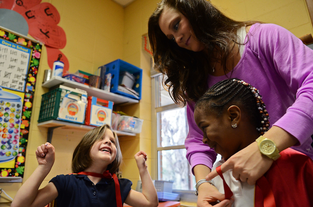 Miss Mississippi Anna Beth Higginbotham helps kindergartner Makhenzi Donaldson, 5, right, put on a super-hero cape while Alayna Bryant, 5, shows off her muscles on Friday morning at Oak Grove Primary School. Higginbotham spoke to the students about good health habits as part of her Miss Mississippi platform. Bryant Hawkins/The Hattiesburg American