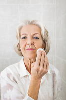 Portrait of senior woman applying face powder in bathroom