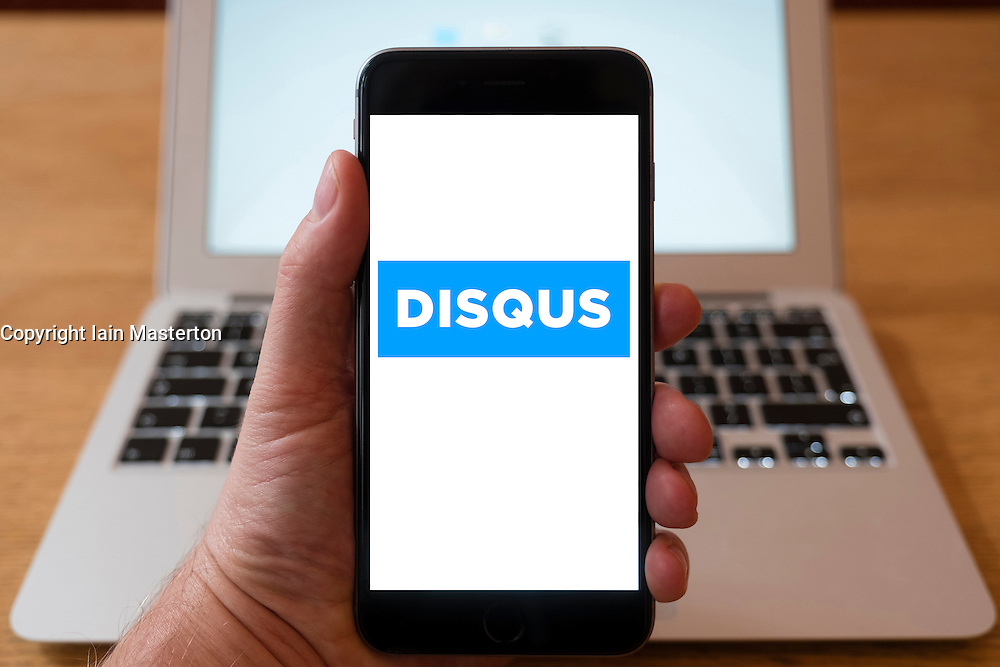 Using iPhone smartphone to display logo of Disqus, a worldwide blog comment hosting service for web sites and online communities
