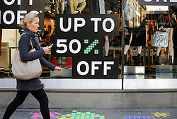 "© Licensed to London News Pictures. 25/11/2016. London, UK. A woman walks past a 50% off sale sign on Oxford Street, central London on ""Black Friday"". Sales from this years Black Friday event are expected to top £2 billion. Photo credit: Tolga Akmen/LNP"
