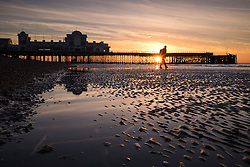© Licensed to London News Pictures. 03/10/2016. Southsea, Hampshire, UK.  A photographer on the beach as the sun rises over South Parade Pier in Southsea this morning, 3rd October 2016. People out enjoying the sunrise enjoyed a cool but clear morning on what is to be another dry and sunny autumn day in the south of England. Photo credit: Rob Arnold/LNP