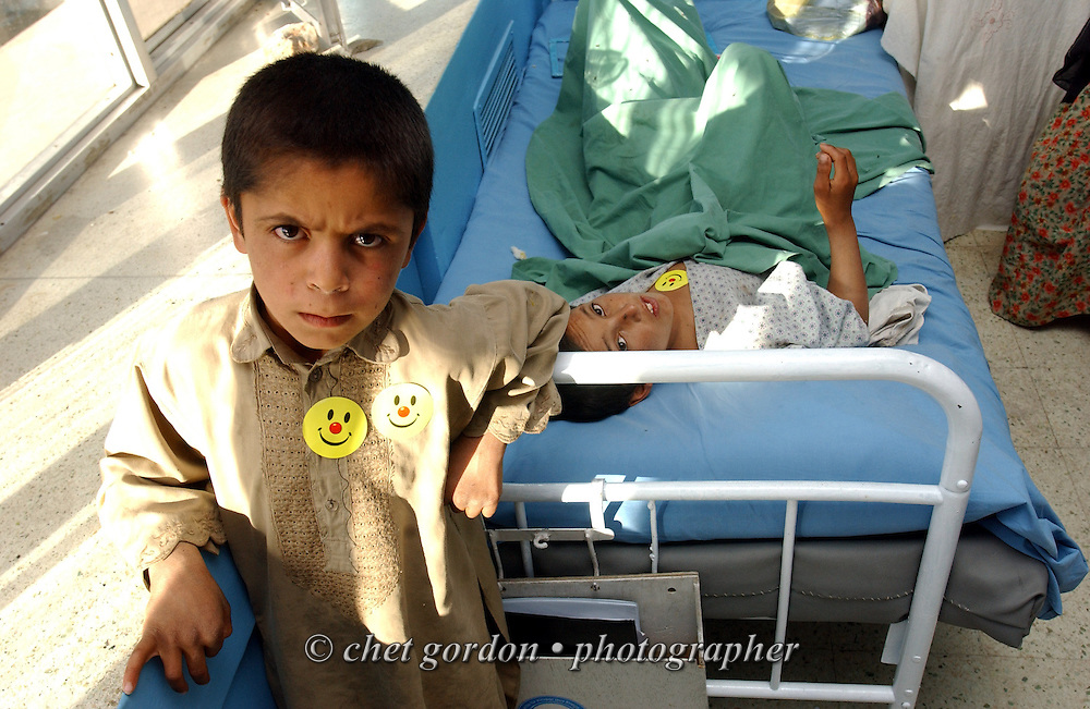 "A young Afghan boy pauses by the bedside of a fellow patient in the Orthopedic Chidren's Ward of the Indira Ghandi Children's Hospital in Kabul on Friday, May 24, 2002. The Geshundheit Instititute, founded by Dr. Hunter ""Patch"" Adams, Lufthansa Cargo, and DHL Worldwide Express collaborated to ship medicines, food and orthopedic supplies to the Indira Ghandi Children's Hospital, clinics and orphanages in Kabul. The German NGO (Non Governmental Organization) Hammer Forum supervised the distribution of the donated supplies from various non-profit organizations in the U.S. and The Netherlands."
