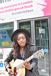 © Licensed to London News Pictures. 21/07/2017. London, UK. Musician Modupe Obasola performs in front of a bus with featuring her image ahead of Dire Straits frontman Mark Knopfler unveiling two iconic London buses outside Wembley Stadium to celebrate launch of Gigs, in association with Gibson, on the eve of International Busking Day. The buses feature pictures of artists Kal Lavelle, Jay Johnson and Modupe Obasola who have all taken part in the Mayor of London's annual busking competition.    Photo credit : Stephen Chung/LNP