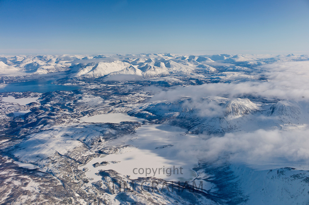 Aerial view of arctic landscape, frozen lakes and the Lyngen Alps from aircraft approaching Tromso in the Arctic Circle in Northern Norway