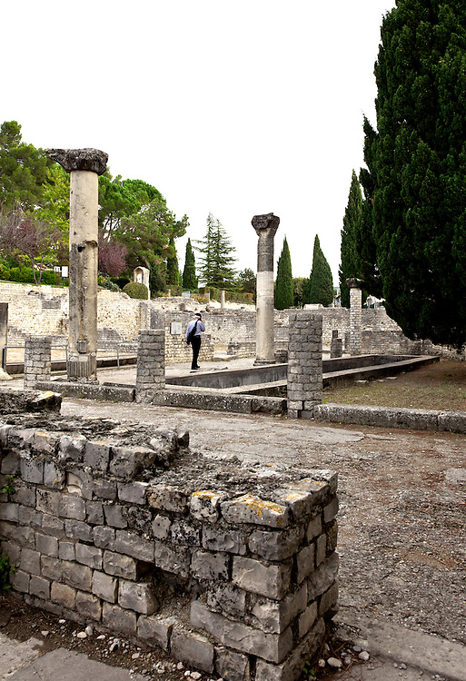Tourist using an audioguide in the Roman ruins of Puymin in Vaison-la-Romaine, Ventoux, Provence, France.