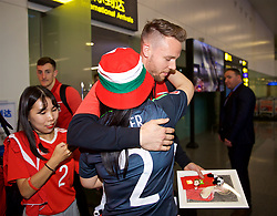 NANNING, CHINA - Monday, March 19, 2018: Wales' Chris Gunter is presented with a drawing by a supporter as the team arrive at Nanning International Airport for the 2018 Gree China Cup International Football Championship. (Pic by David Rawcliffe/Propaganda)