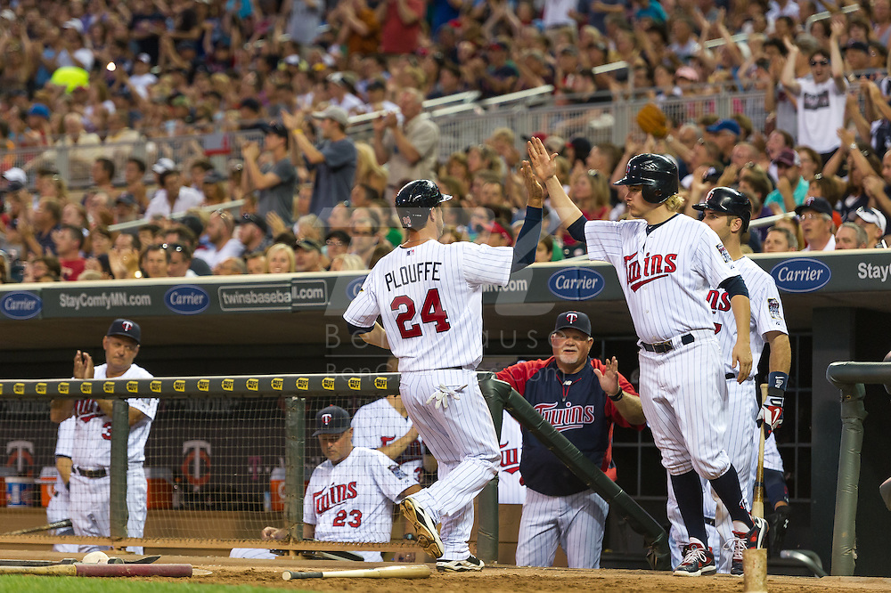 Trevor Plouffe #24 of the Minnesota Twins is congratulated in the dugout after scoring against the Kansas City Royals on June 27, 2013 at Target Field in Minneapolis, Minnesota.  The Twins defeated the Royals 3 to 1.  Photo by Ben Krause