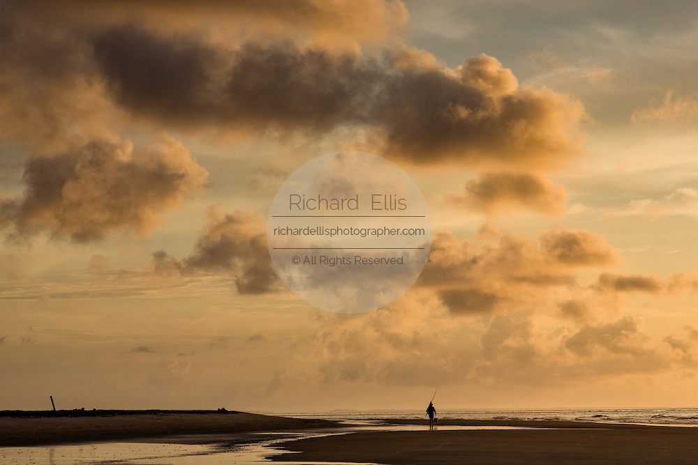 A fishermen walks along the beach at dawn on Isle of Palms at Wild Dunes near Charleston, South Carolina.
