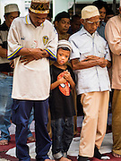 06 JULY 2016 - BANGKOK, THAILAND:  A boy stands with the men praying during Eid services at Ton Son Mosque in the Thonburi section of Bangkok. Eid al-Fitr is also called Feast of Breaking the Fast, the Sugar Feast, Bayram (Bajram), the Sweet Festival or Hari Raya Puasa and the Lesser Eid. It is an important Muslim religious holiday that marks the end of Ramadan, the Islamic holy month of fasting. Muslims are not allowed to fast on Eid. The holiday celebrates the conclusion of the 29 or 30 days of dawn-to-sunset fasting Muslims do during the month of Ramadan. Islam is the second largest religion in Thailand. Government sources say about 5% of Thais are Muslim, many in the Muslim community say the number is closer to 10%.       PHOTO BY JACK KURTZ