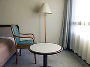 hotel room in the morning with one chair which faces the window