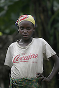 Pygmy women wearing westernised clothes. Head scarf of English football team Arsenal and Tshirt reads cocaine. Borders of Bwindi forest Impenetrable national park. Uganda. Africa.