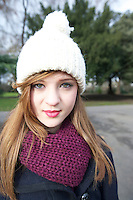 Portrait of beautiful young woman wearing scarf and knit cap