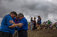 Three men hold their arms as they share a moment of prayer outside Marjory Stoneman Douglas High School where a memorial was set up to honor the 17 students and staff killed on Valentine's Day by school shooter Nikolas Cruz.<br /> <br /> by Samuel Navarro