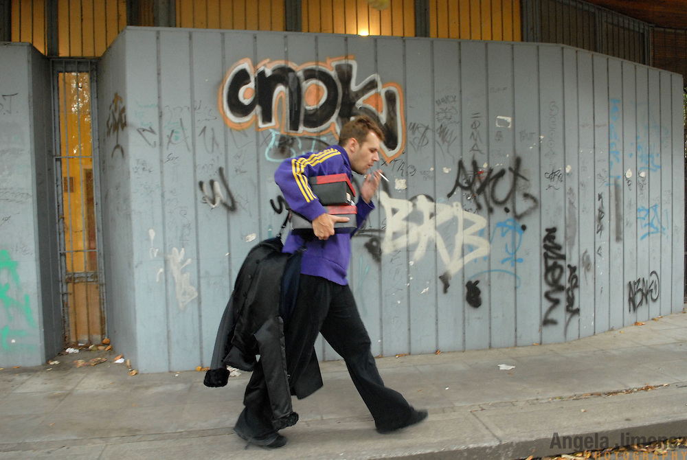 """World Champion same-sex ballroom dancer Robert Tristan Szelei walks past graffiti on the wall of a dance lesson facility in a communist-era section of Budapest, Hungary on October 20, 2006, holding costumes and competition numbers he retrieved there for competitors in the 2nd annual World Championship Same-Sex Ballroom Dancing competition, which he competed in and helped host in his hometown on October 21, 2006. ..Szelei and Gergely Darabos, who are known as the """"Black Swans,"""" are the reigning world champions in men?s Latin same-sex ballroom dancing. They have been training and preparing to host the 2nd annual World Championship and the Csardas Cup, the first-ever Eastern European same-sex ballroom competition, both held at the Korcsarnok arena.  This is the pinnacle event of the blossoming same-sex ballroom scene...Szelei and Darabos went on to win the men?s Standard division and finished fourth in the Latin division. ..The event was organized by the US-based World Federation of Same-Sex Dancing, which hosted the first World Championship Same-Sex championships in 2005 in Sacramento, California. The Black Swans did a large amount of the coordination and planning in Budapest, a city that had never seen an event of this kind. When government funding fell through, they secured funding from patron Desire (accent on the ?e?) Dubounet, owner of the local Club Bohemian Alibi drag club. ..The World Championship events are newly recognized, but same-sex dancers have been competing on a national and international circuit for a number of years, especially in Europe, including at the Eurogames, the Gay Games, the London Pink Jukebox Trophy and the Berlin Open, among others. Countries including the United States, the Netherlands, Germany and, now, Hungary, hold their own national same-sex championships. Hungary held its first national championships in April 2006...Szelei and Darabos spent three months at the Sacramento Dancesport same-sex dance school in California this summer,"""