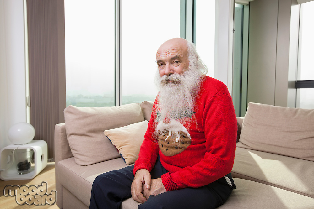 Portrait of senior man sitting on sofa bed