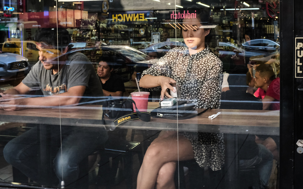 Pretty Asian girl sitting in café window with street reflections.