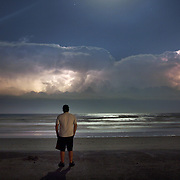 A man watches a storm system moving over Wrightsville Beach, NC