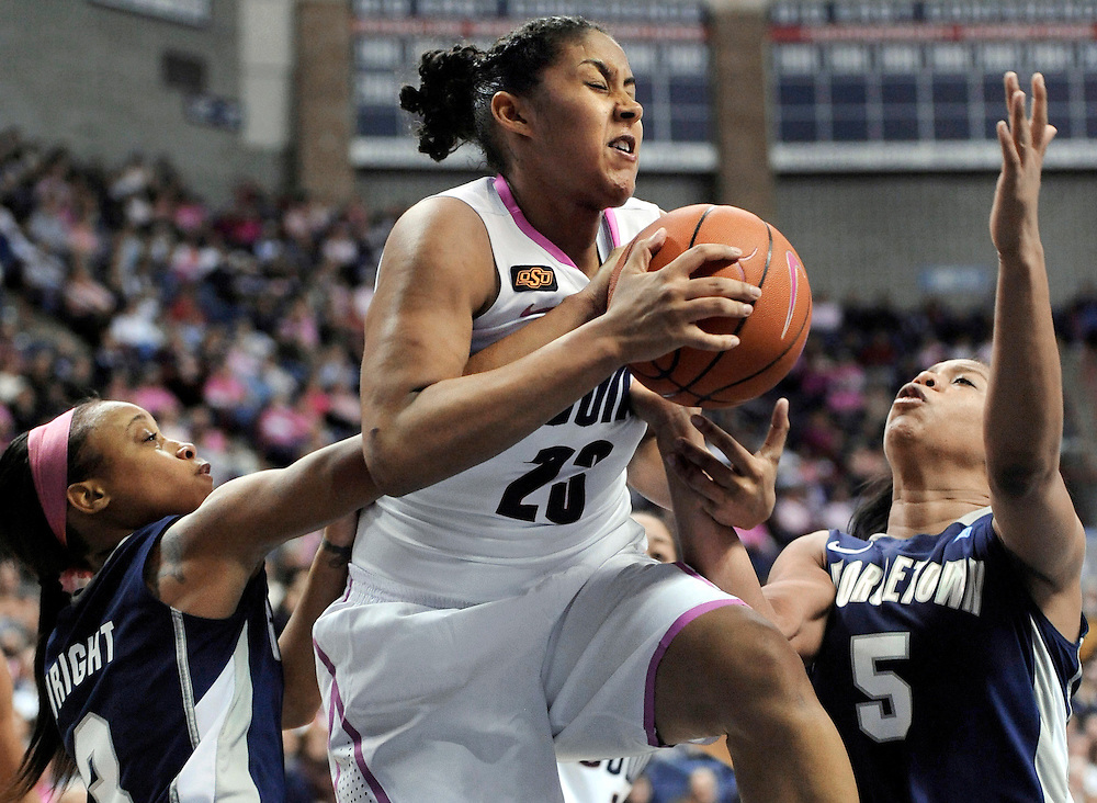 Connecticut's Kaleena Mosqueda-Lewis, center, battles for a rebound against Georgetown's Rubylee Wright, left, and Adria Crawford, right, in the second half of an NCAA college basketball game in Storrs, Conn., Saturday, Feb. 11, 2012.  Mosqueda-Lewis was top-scorer for Connecticut with 23 points. Connecticut won 80-38. (AP Photo/Jessica Hill)