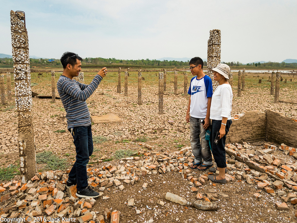 02 APRIL 2016 - NA SAK, LAMPANG, THAILAND:  A Thai family stops for pictures in the ruins of a public building in Sobjant village. The village of Sobjant in Na Sak district in Lampang province was submerged when the Mae Chang Reservoir was created in the 1980s. The village was relocated to higher ground a few kilometers from its original site. The drought gripping Thailand drained the reservoir and the foundations of the Buddhist temple in the original village became visible early in 2016. Thai families come down to the original village to pray in the ruins of the temple and look at what's left of the village. This is the first time in more than 30 years that this area has not been under two meters of water.     PHOTO BY JACK KURTZ