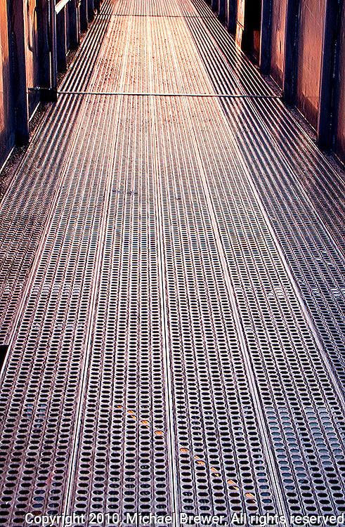 Golden metallic grid passageway at Werdhölzli Sewage Treatment Plant, Zürich, Switzerland.