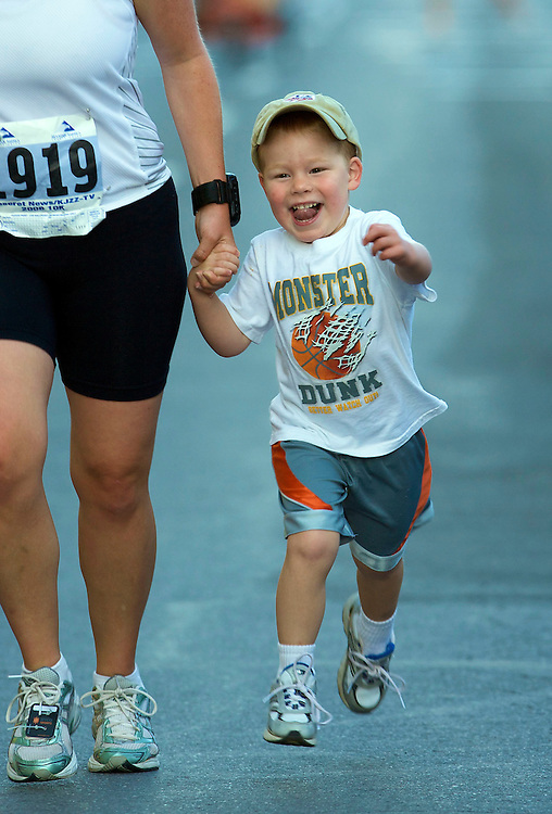 Lindi Salmond and her son Caleb of Bountiful, Utah cross the finish line of the 10K Race sponsored by the Deseret News at Liberty Park July 24, 2008 in Salt Lake City, Utah. August Miller/ Deseret Morning News .